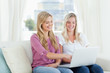 Laughing women sitting on the couch looking at a laptop