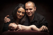 Mixed Race Couple Lovingly Look On While Baby Lays on Pillow