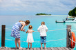 Mother and kids sitting on wooden dock
