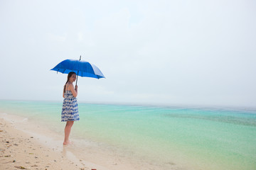 Woman at beach under rain