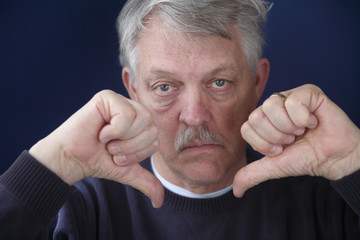 an older man with both thumbs down