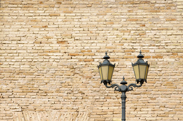 Old style street lamp in front of the wall of yellow bricks
