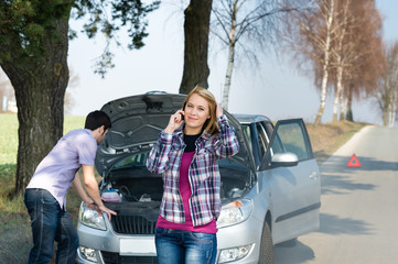 Car breakdown couple calling for road assistance