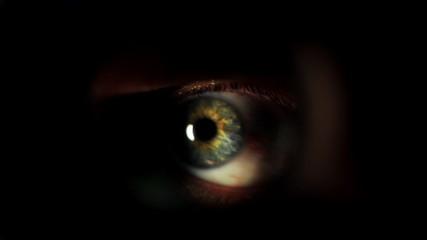 Mans eye looking through a blured hole