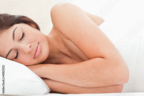 A close up view of a woman sleeping with her head on the pillow