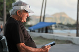 Elderly man reads ebook on bench by beach
