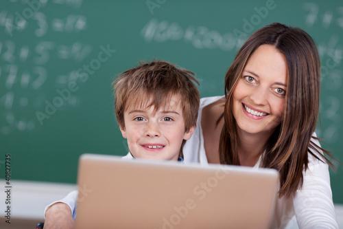 lehrerin und schulkind arbeiten am laptop