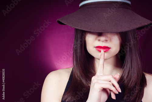 Young beautiful woman showing silence sign