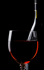 red wine in glass and bottle isolated on black