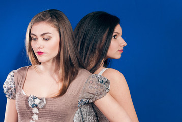 Beautiful young women together back to back on blue background