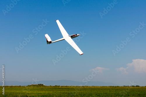 Leinwanddruck Bild Glider flying on a blue sky