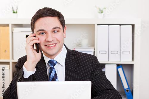 Geschäftsmann im Büro mit Handy