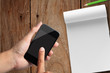 business hand  with smart phone and note paper on wooden table