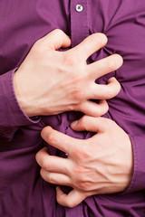 Krampfende Hände halten Bauch