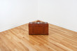 Vintage leather suitcase in empty room corner