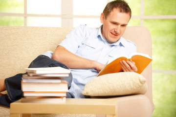 Man reading book in home