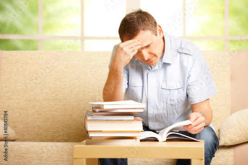 Man reading book on sofa