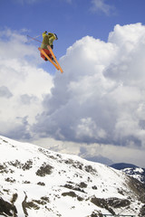flying skier on mountains, in cloudy sky