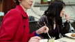 Two female friends talking and eating lunch in restaurant