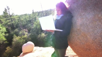 Girl with laptop in natural park, mountain