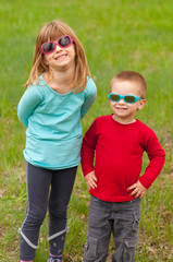 Brother and sister posing outside with sunglasses