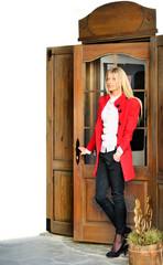 Woman in red suit opening door