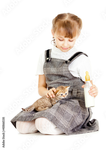Girl feeding British kitten isolated on white