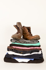Old Clothes And A Pair Of Boots For Charity Or Jumble Sale