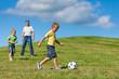 Glückliche Familie spielt Fußball im Sommer