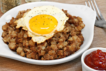 Fried egg on top of roast beef hash.