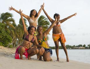4 jeunes filles sur la plage les bras en l'air