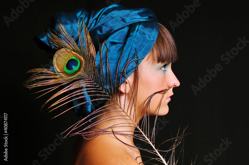 Young woman in blue turban with peacock feather