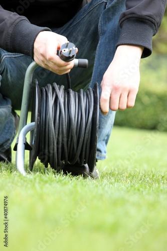Gärtner rollt Kabeltrommel auf (Ausschnitt)