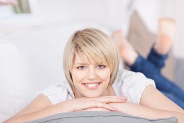 lächelnde blonde frau liegt auf dem sofa