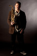 Jazzman standing with saxophone on dark background