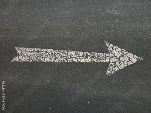 Weißer Pfeil als Fahrbahnmarkierung auf einem Parkplatz