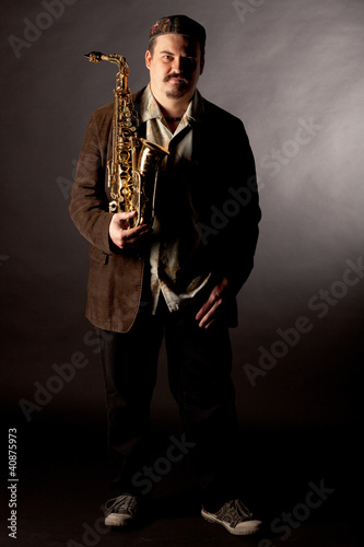Jazzman standing with saxophone on dark background