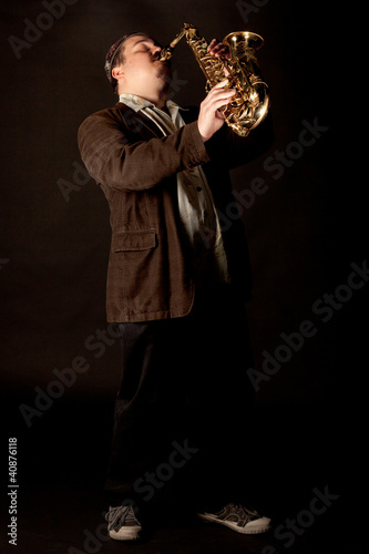 Jazzman standing playing saxophone on a dark background, low key