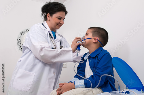Doctor applying oxygen treatment on a little boy with asthma.