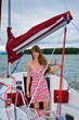 Beautiful girl in light dress standing on the deck of sailboat