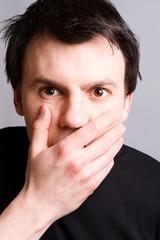 schockierter mann hält die hand vor dem mund