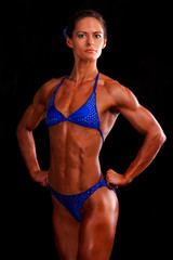 muscular woman posing against black background.