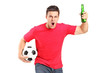 A portrait an euphoric fan holding a beer bottle and football