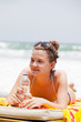 girl lies on  beach plank bed and holds  bottle with  water