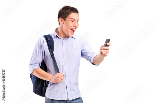 A portrait of a smiling young man looking at a cell phone