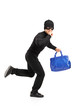 Thief running with a stolen purse and finger on lips gesturing s