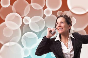 Telefonierende Geschäftsfrau vor buntem Hintergrund