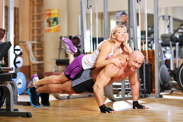 Instructor is doing push-ups with his female co-worker behind th