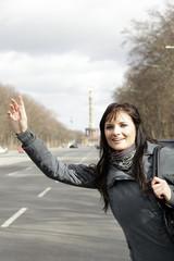 junge Frau winkt nach einem Taxi