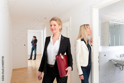 Leinwanddruck Bild Paar bei Besichtigung von Wohnung mit Maklerin